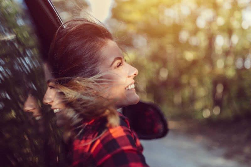 Frau ist glücklich mit ihrem neuen Leasingauto