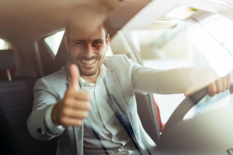 Zufriedener Mann in seinem Leasingwagen