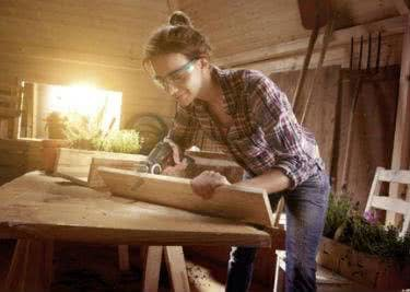 Eine Frau bearbeitet Holz auf einer Werkbank