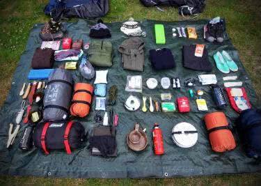 Camping Ausrüstung ausgebreitet auf einer Plane