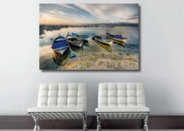 Zwei weiße Stühle stehen vor einem Gemälde.