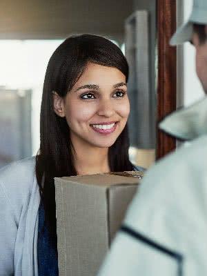 Frau übergibt Paketboten ein Paket